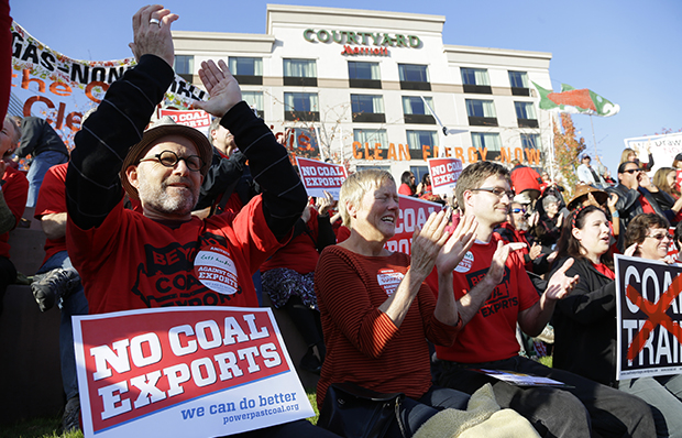 Russ Childers, left, of Seattle, sits among other protesters as they demonstrate against trains carrying coal for export moving through Washington state on Thursday, October 17, 2013, in Tacoma, Washington.
