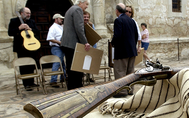 Fess Parker, who gained fame for his portrayal of Davy Crockett in the 1950s Walt Disney TV series, center, visits with Alamo director David Roberts, right, after he presented a 180-year-old Kentucky long rifle to the Alamo for its collection at the Alamo in San Antonio, Friday, March 5, 2004.