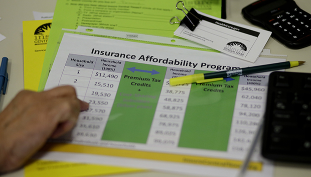A volunteer counselor with Insure Central Texas uses a chart to help explain health insurance options, Tuesday,  October 1, 2013, in Austin, Texas.