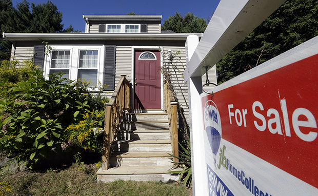 "A ""for sale"" sign hangs in front of a house in Walpole, Massachusetts, Wednesday, September 18, 2013."