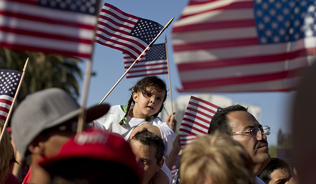 Demonstrators wave American flags as they march down Las Vegas Boulevard during an immigration rally, Wednesday, May 1, 2013, in Las Vegas, Nevada. A new CAP poll shows that Americans are more open to diversity than media and politics would lead us to believe.