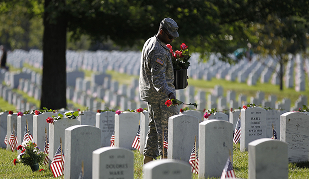 A soldier places roses on grave stones at Arlington National Cemetery in Arlington, Virginia.