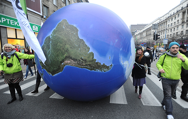 Climate activists roll a giant globe during an environmentalist march to campaign against global warming in downtown Warsaw, Poland, Saturday, November 16, 2013.