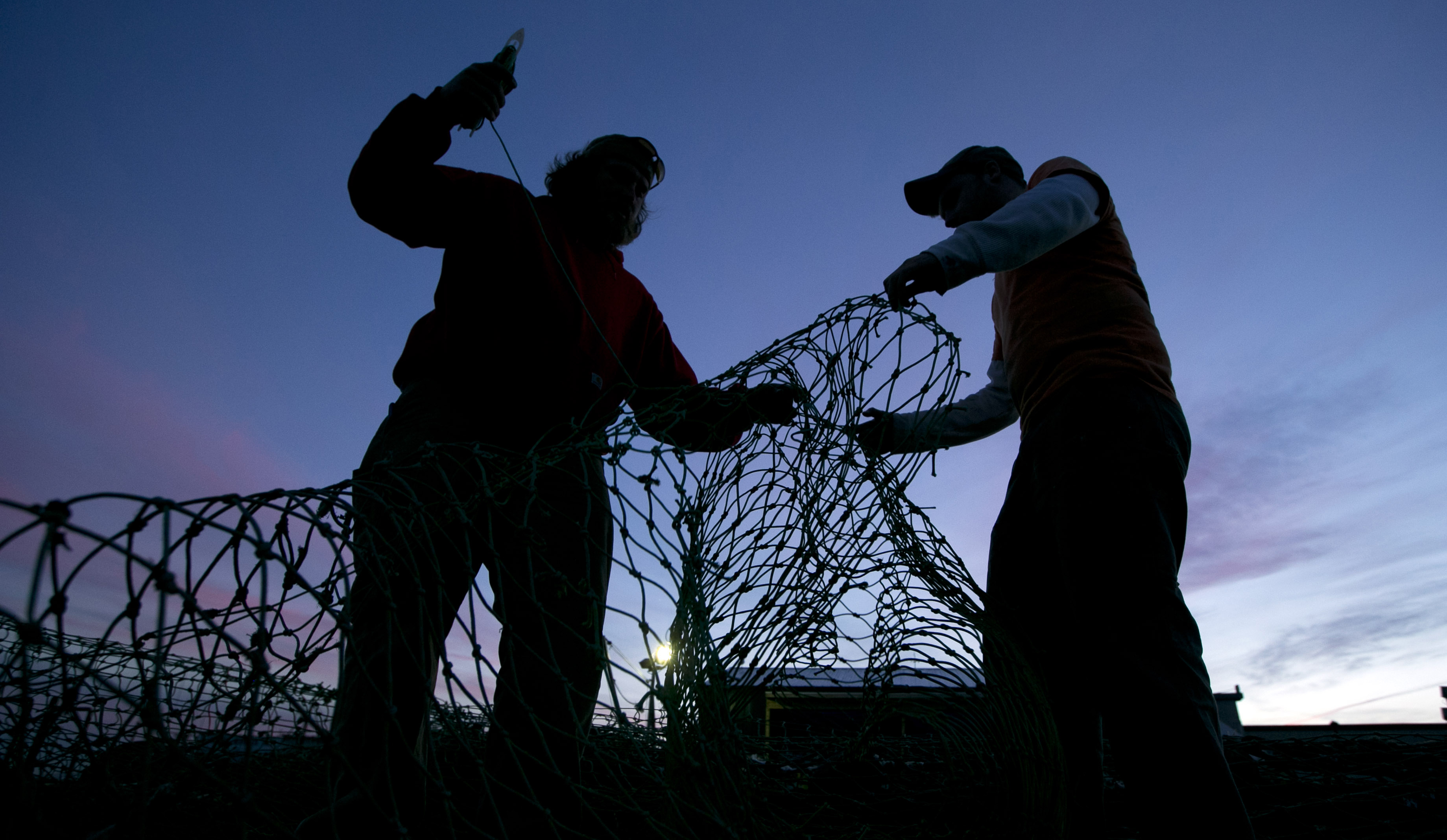 Fishermen Lucas Dewildt and Dillon Robbins mend groundfishing nets in Portland, Maine.
