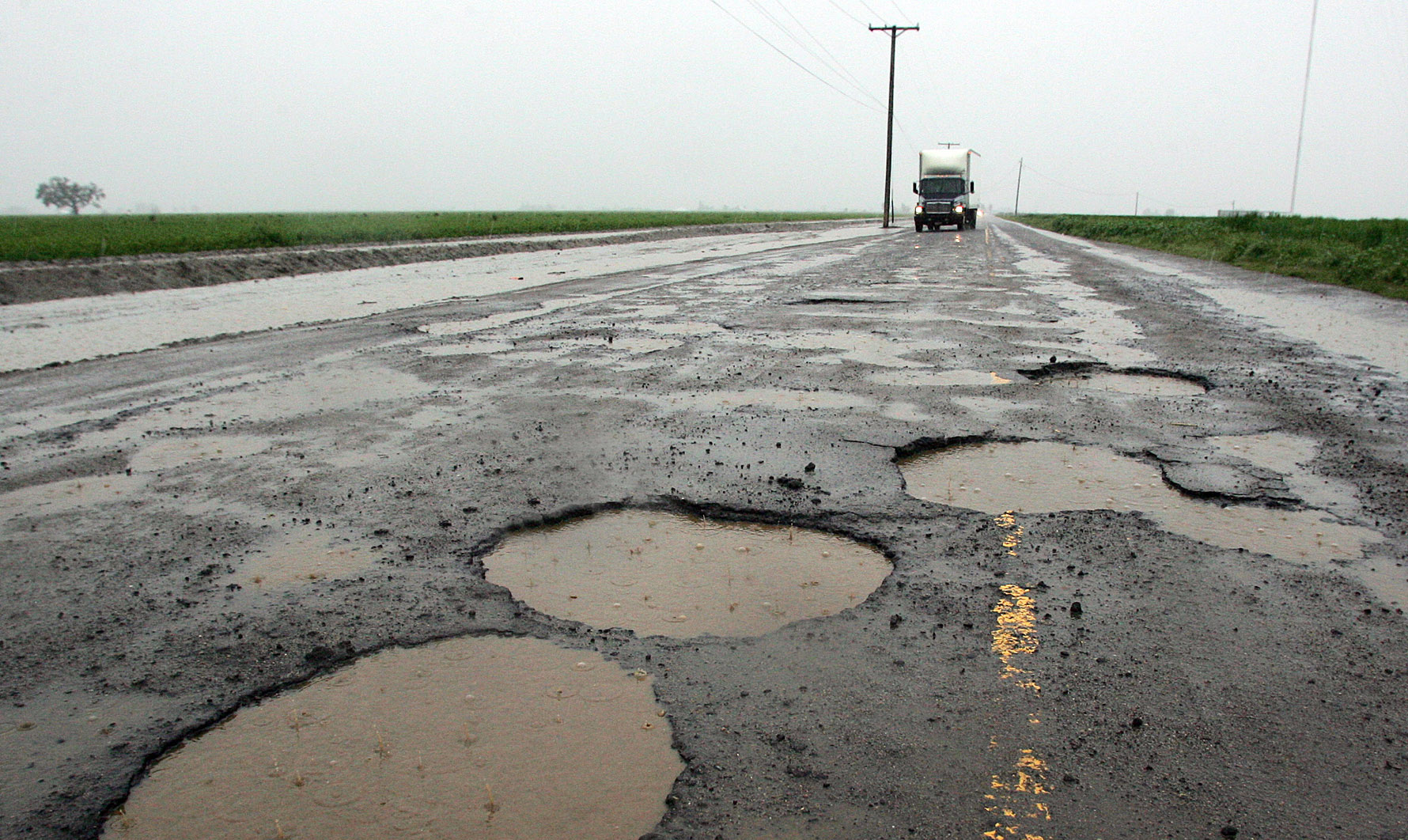 Potholes are visible on a farming back road in Tulare, California.