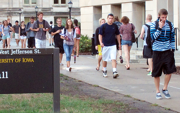 In this 2012 photo, students walk between classes on campus at the University of Iowa in Iowa City, Iowa.