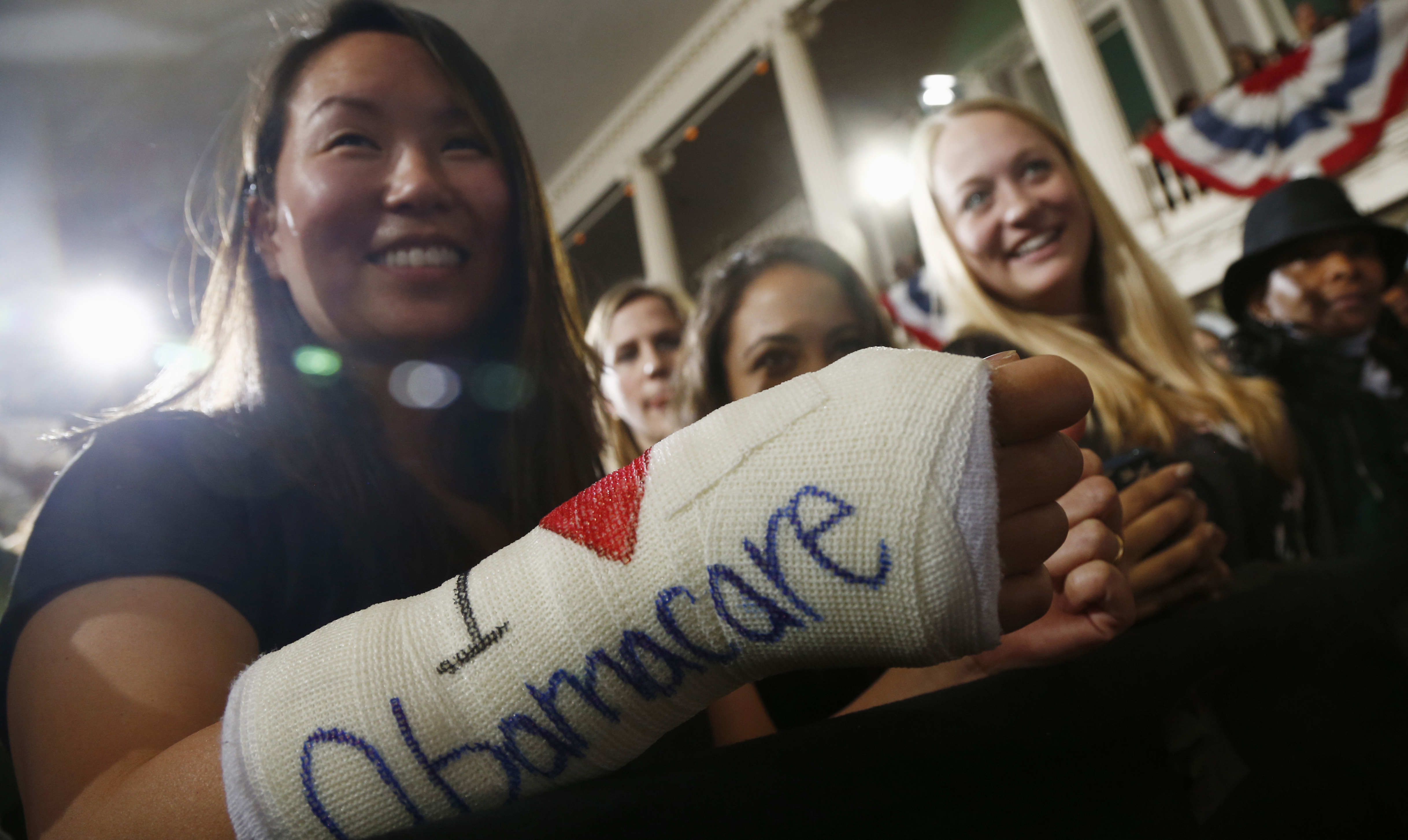 "Cathey Park shows the words ""I Love Obamacare"" on her cast as she waits for President Barack Obama to speak at Boston's historic Faneuil Hall about the federal health care law."