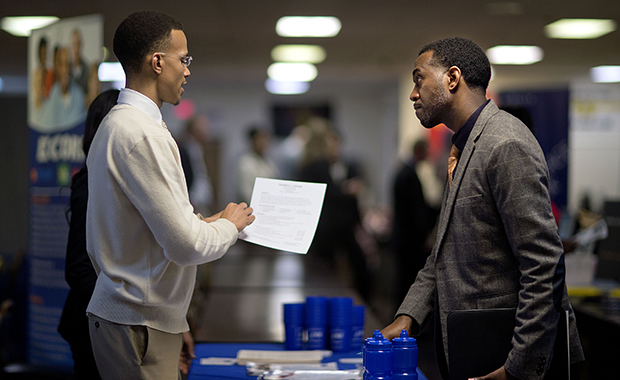 U.S. Air Force Master Sgt. Thomas Gipson, of Atlanta, right, has his résumé looked over by Ralph Brown, a management and program analyst with the Centers for Disease Control and Prevention, during a job fair for veterans at the VFW Post 2681, Marietta, Georgia, Thursday, November 14, 2013.