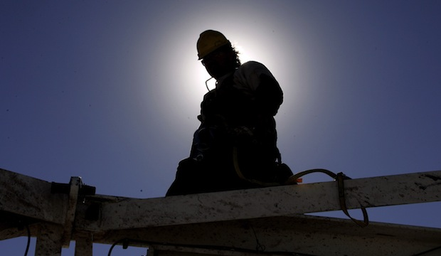 A worker is silhouetted by the sun as he helps dismantle an oil rig to move it to a new drilling site at a site near Elk City, Oklahoma.