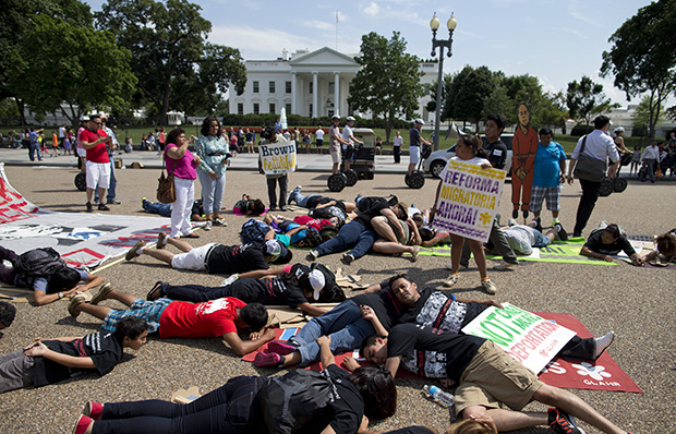Demonstrators lie down in front of the White House in Washington, Wednesday, July 24, 2013, during a demonstration to signify family members deported, as they rallied in favor of immigration reform.