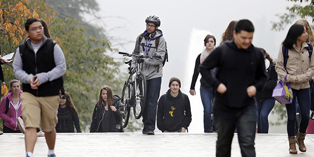 In this photo taken Tuesday, October 15, 2013, University of Washington students walk between classes on the campus in Seattle.