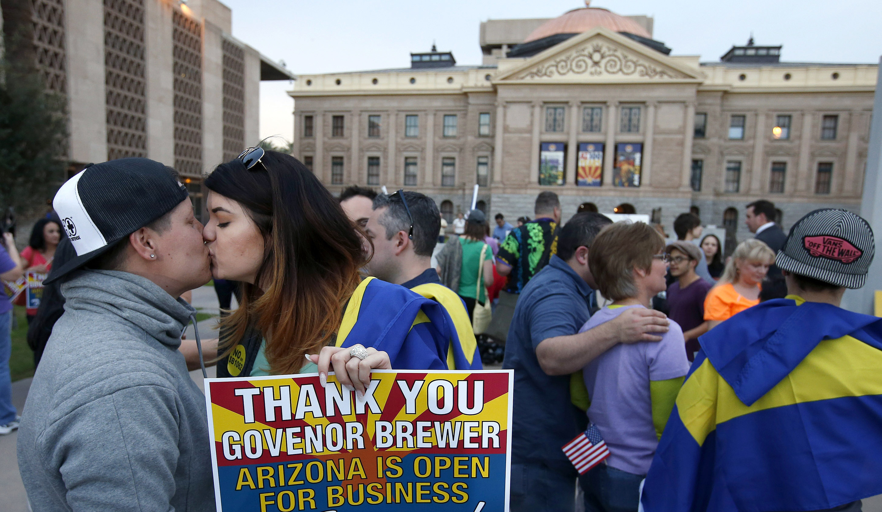 With the Arizona State Capitol in the background, LGBT rights supporters  Jo Jo Halko and Rachel Butas kiss after learning that Gov. Jan Brewer vetoed an anti-gay bill.