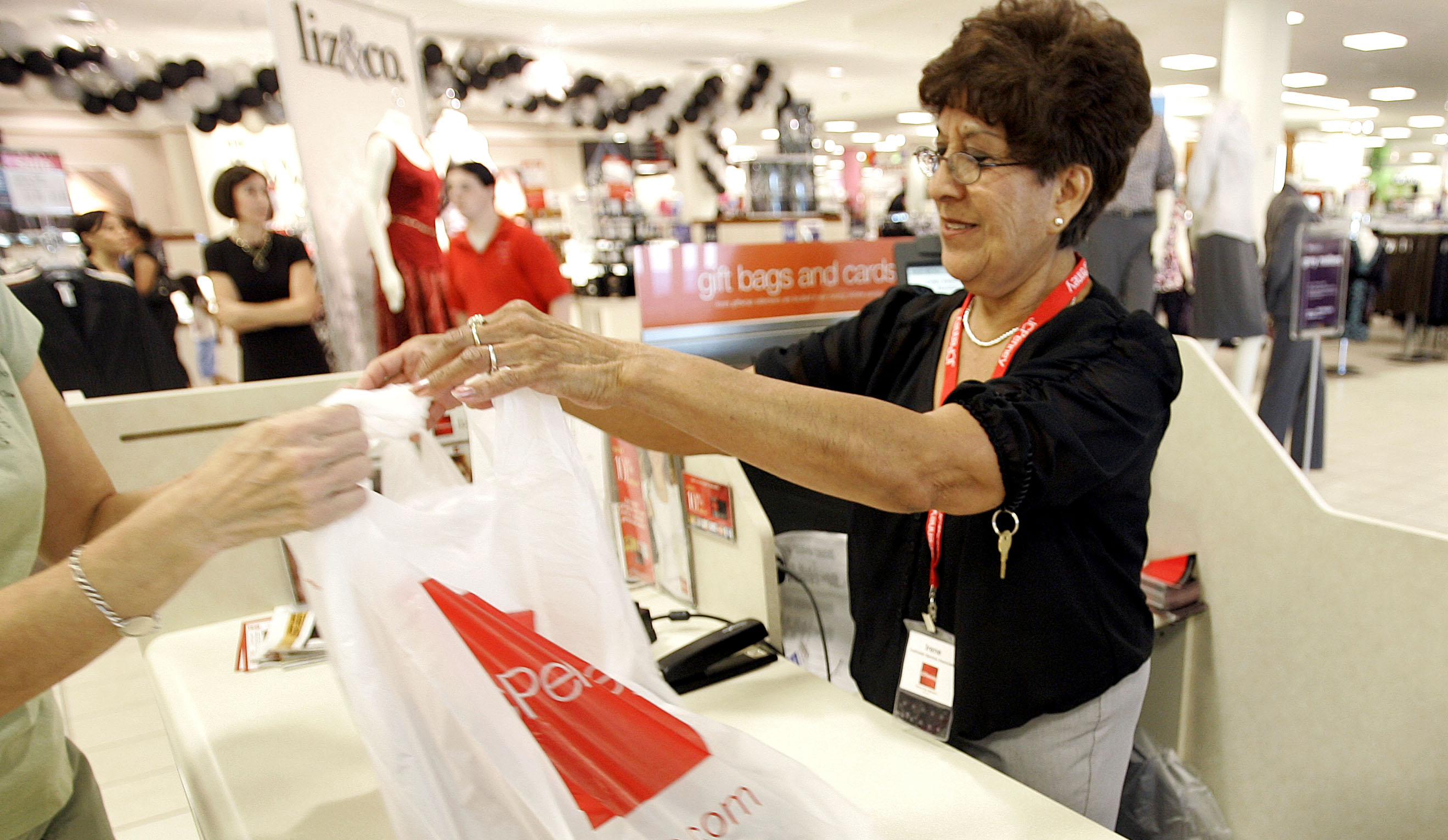 Cashier Irene Peters checks out a customer at a department store in Phoenix.