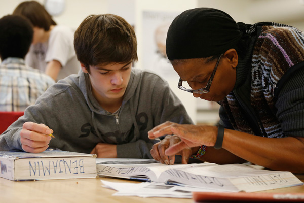 Student James Montalbano, 11th grade, works with teacher Angela Benjamin in the Advanced Placement Physics class at Woodrow Wilson High School in Washington, Friday, February 7, 2014.