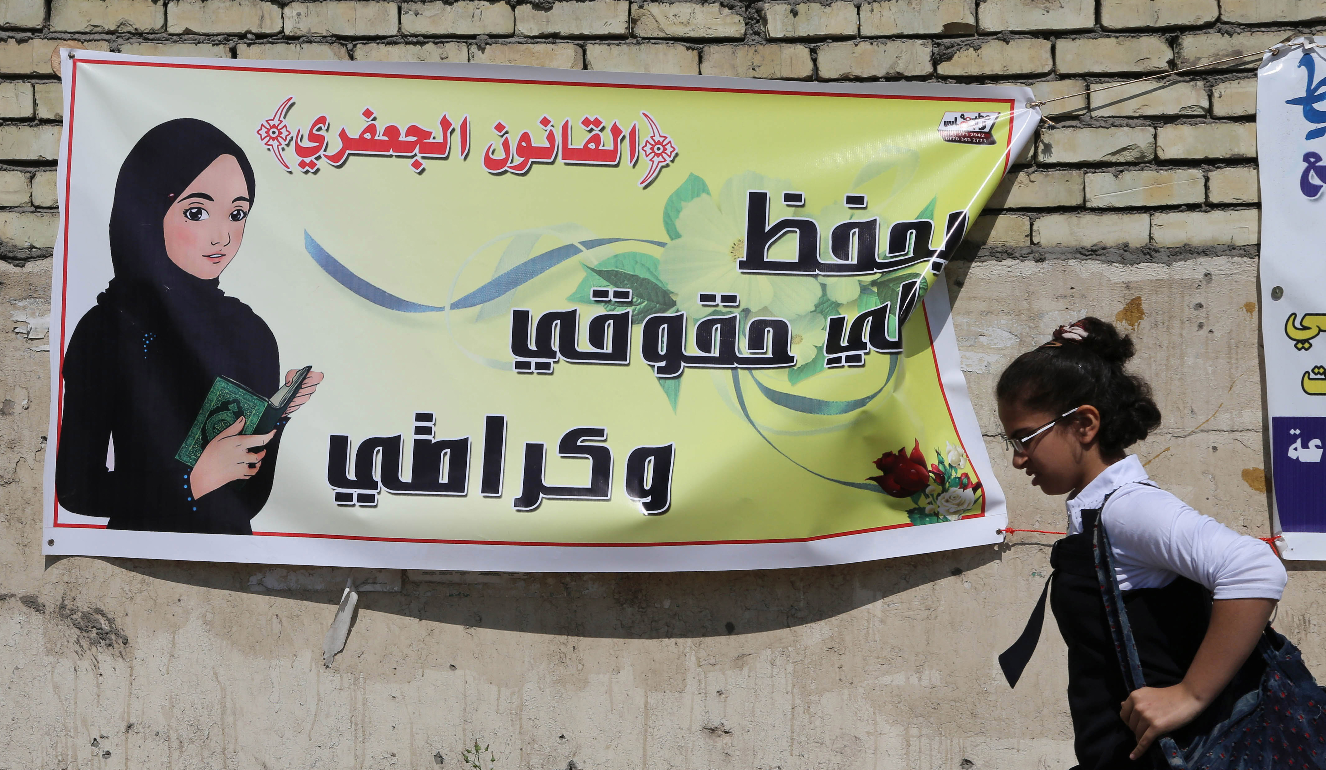 """A schoolgirl passes a banner for the Jaafari personal status law in Baghdad. The Arabic on the banner reads, """"The Jaafari personal status law saves my rights and my dignity."""""""
