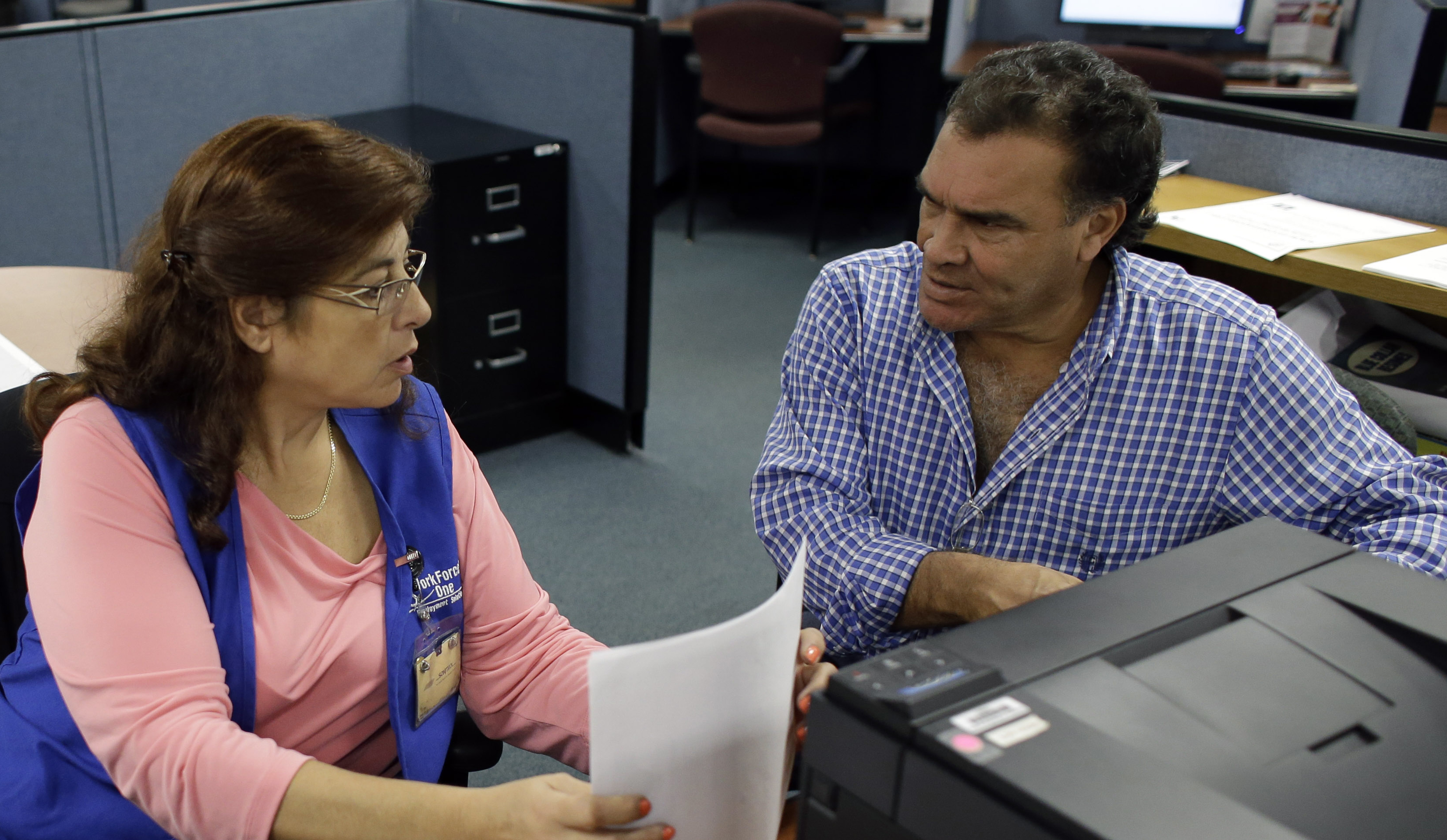 Rose Capote-Marcus, left, helps Waldemar Vega with problems he is having receiving his unemployment benefits at WorkForce One in Davie, Florida.