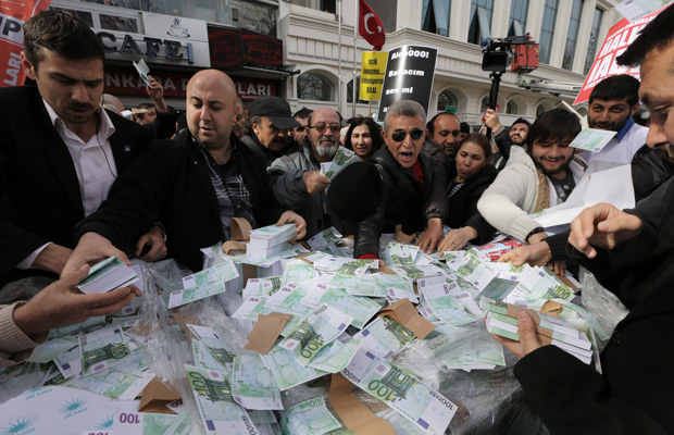 Members of the main opposition Republican People's Pary, CHP, distribute 30 millions fake Euro bills during an anti-government protest denouncing a corruption scandal in Ankara, Turkey, March 1, 2014.
