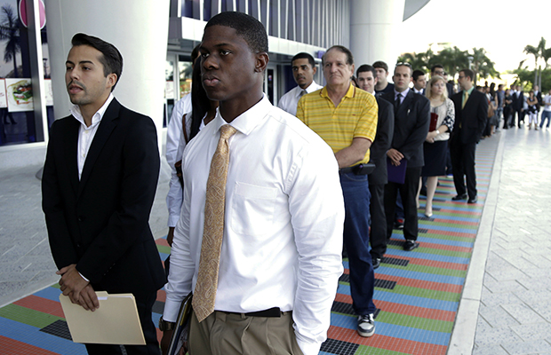 Luis Mendez, 23, left, and Maurice Mike, 23, wait in line at a job fair held by the Miami Marlins at Marlins Park in Miami, Florida, on October 23, 2013.