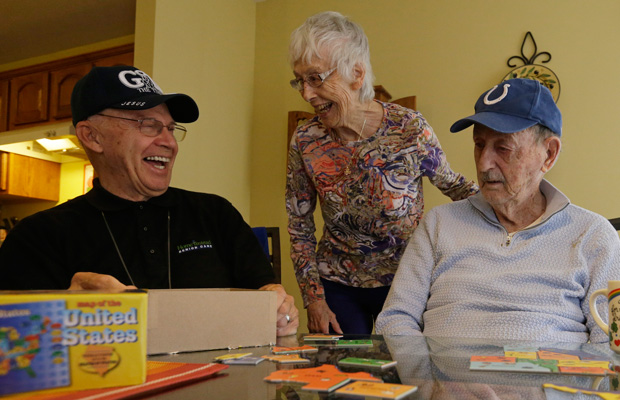 Caregiver Warren Manchess, left, laughs with Paul and Mary Gregoline as they work on a puzzle, in Noblesville Indiana.