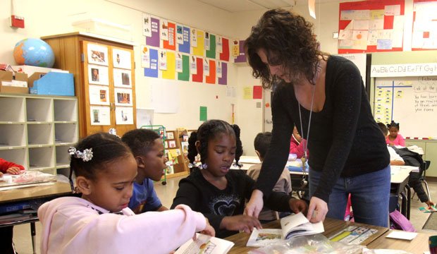 Teacher Lori Peck helps first grader Timia Harris at Grace L. Patterson Elementary school in Vallejo, California.