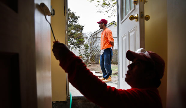 Victoriano Del La Cruz, a carpenter from Mexico, stands just outside of a basement entrance as Sergio Ajche from Guatemala finishes a painting job in New York.