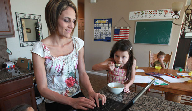 Christine Young works on her laptop, accompanied by two of her six children, Julia, 6, and Noah, 20 months.