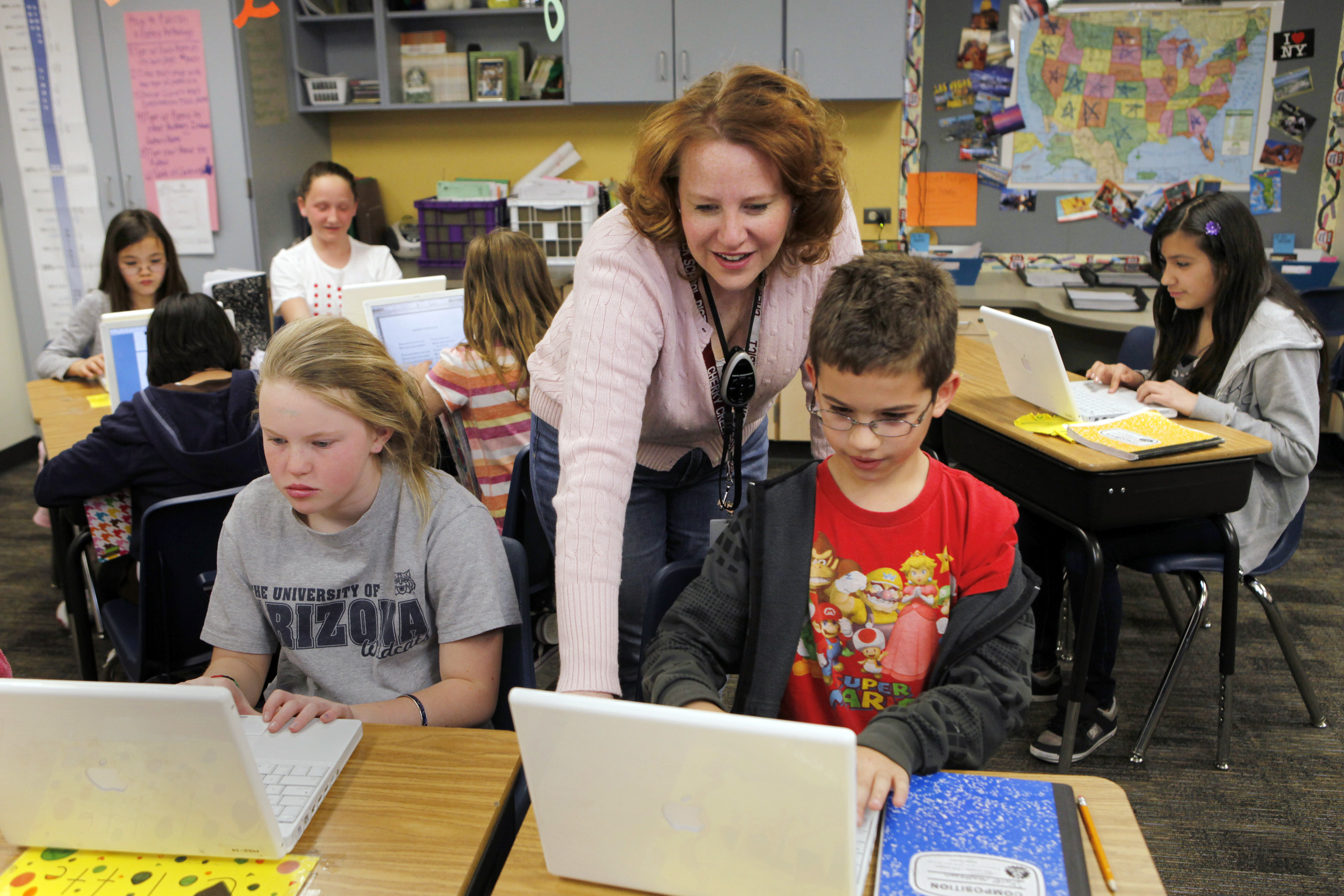High Plains Elementary School teacher Jennifer Williford works with Colette Jackson and Skyler Matteson in her fifth grade class at the Englewood, Colorado school. Colorado has long debated the standardized tests it gives schoolchildren.