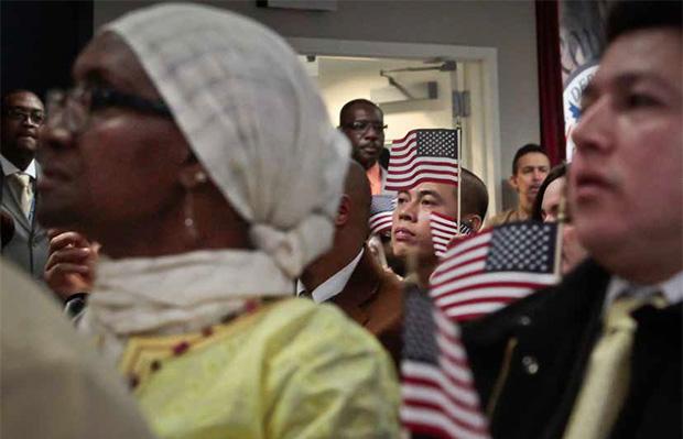 Inmigrantes con banderas miniaturas de los EEUU escuchando al Presidente Barack Obama durante una ceremonia de ciudadania en NY el 18 de diciembre del 2013