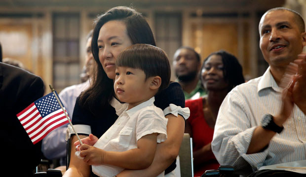 Miyoung Lee, originally from Korea, holds her son, Nate, during a naturalization ceremony at the New York Public Library on July 2, 2014.