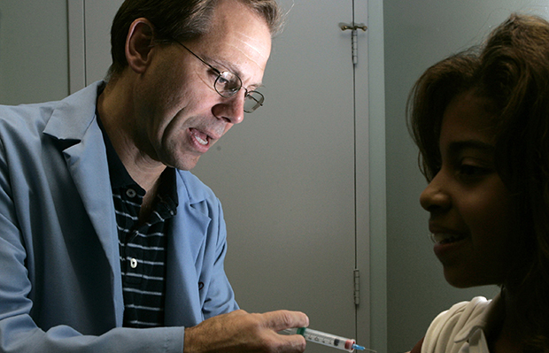 Dr. Donald Brown, left, inoculates 14-year-old Kelly Kent with an HPV vaccine in his Chicago office, August 28, 2006.