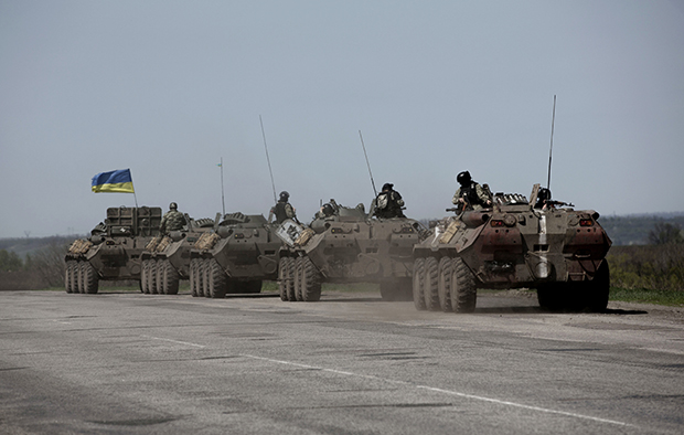 A column of Ukrainian armored vehicles makes its way along the road between Kharkiv and Slovyansk, Ukraine, Thursday, April 24, 2014.