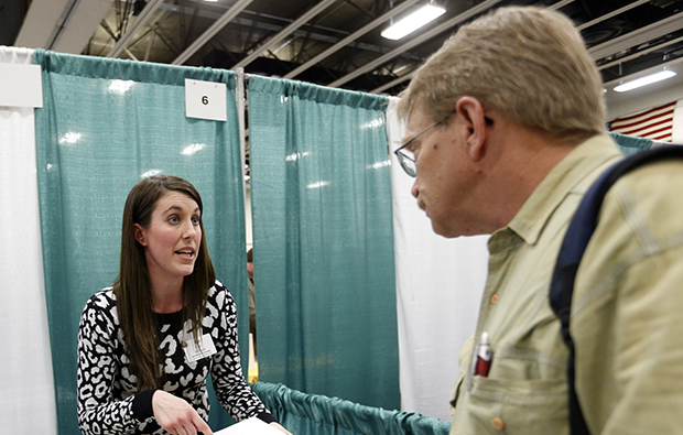 Erin Wilson, of Hannaford Bros. supermarket company, left, talks with a job seeker during a job fair at Columbia-Greene Community College in Hudson, New York, April 22, 2014.