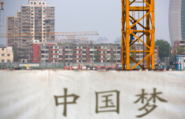 "A worker climbs up a crane at a construction site near a Chinese government billboard with the words ""China Dream"" in Beijing, China."