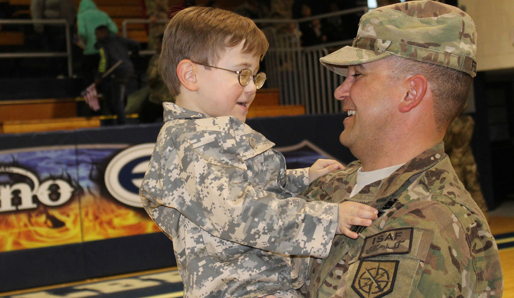 First Lt. Jason Felker holds his son at a January 2014 welcome home ceremony for the Georgia Army National Guard's 1-214th Field Artillery Battalion in Elberton, Georgia.