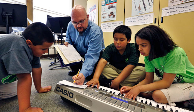 Conrad Kehn helps students compose during music class at Cole Elementary in Denver, Colorado.