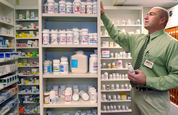 Pharmacist Salvatore Ciolino, Jr. reaches for a prescription bottle at a Gloucester, Massachusetts.
