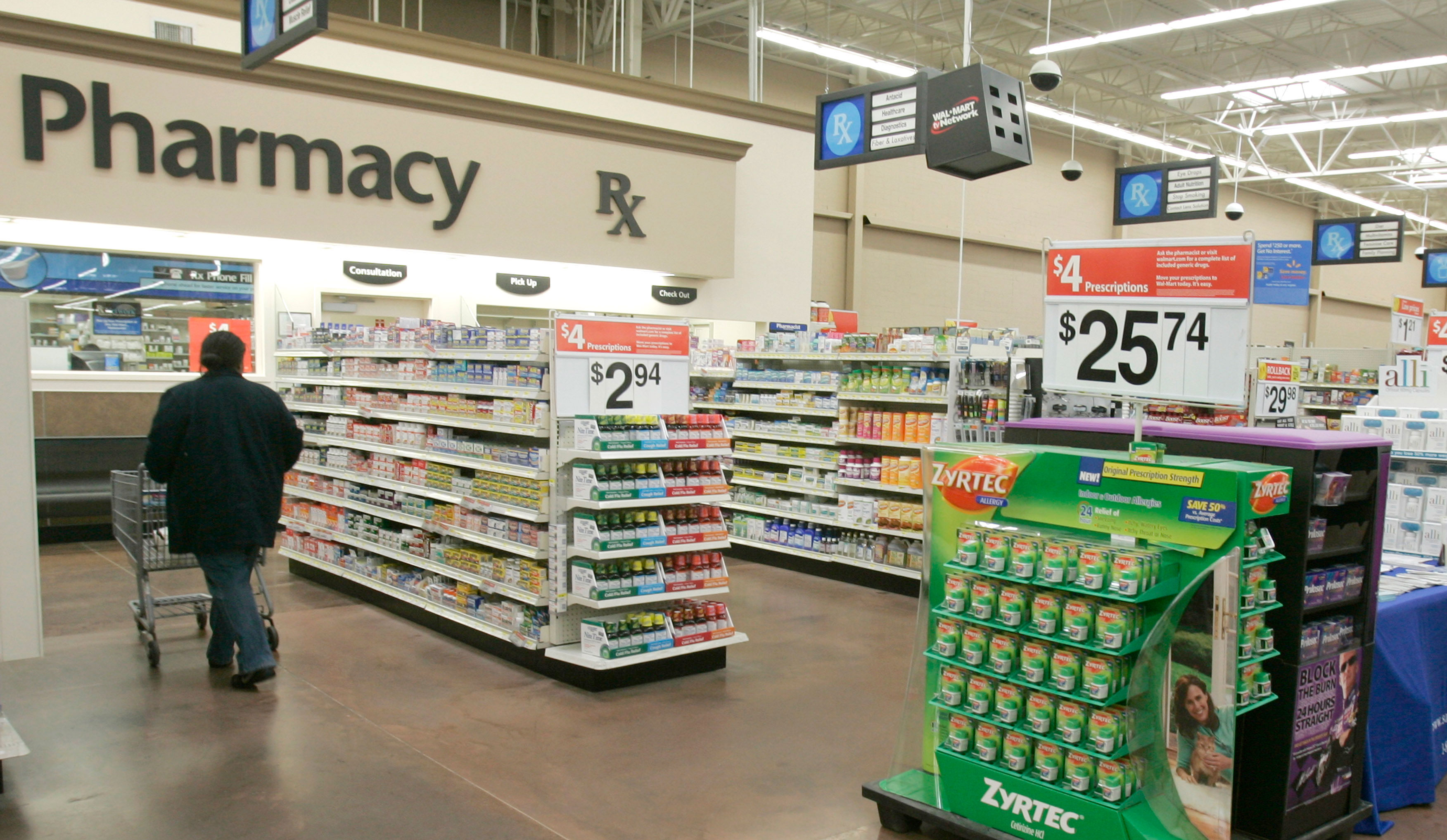 A shopper walks toward the pharmacy at a Little Rock, AK Wal-Mart store.