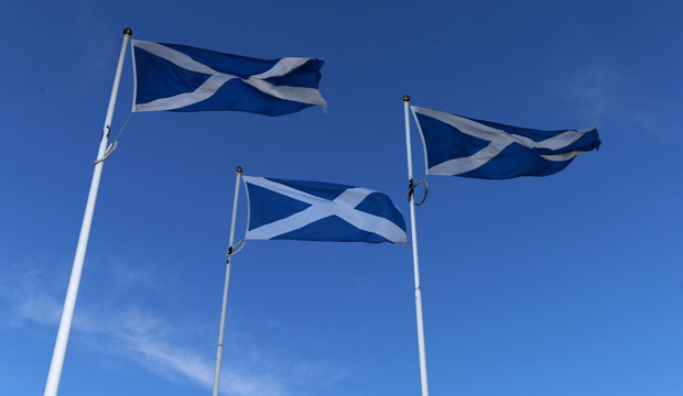 A trio of Scottish Saltire flags are displayed at the Scottish border.