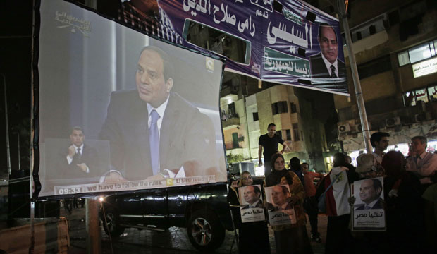 Supporters of former Field Marshal Abdel Fattah al-Sisi watch his first televised interview on a big screen on a street in downtown Cairo, Egypt.