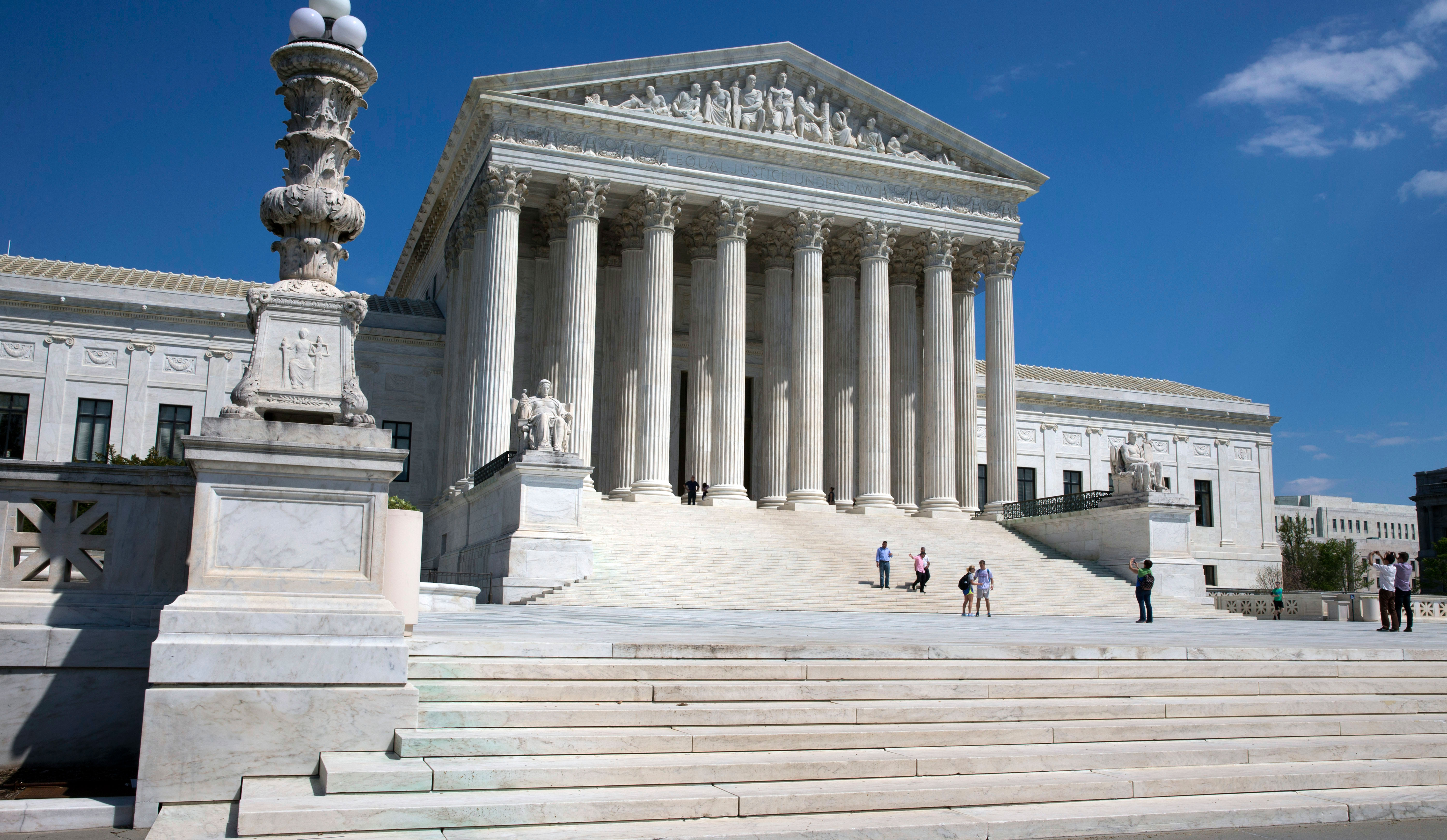 People walk on the steps of the U.S. Supreme Court in Washington, D.C.
