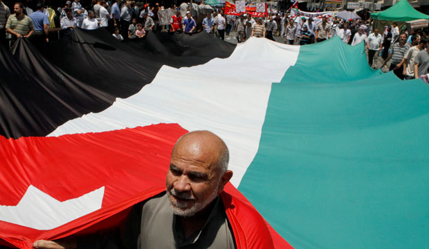 A follower of the Jordanian Muslim Brotherhood movement carries a Jordanian flag during a protest in Amman, Jordan.