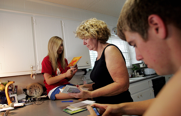 Joretta Beasley, center, goes though mail with her son Scott, 17, and her daughter Natalie, 15, at their home in Burlington, North Carolina, June 2009.