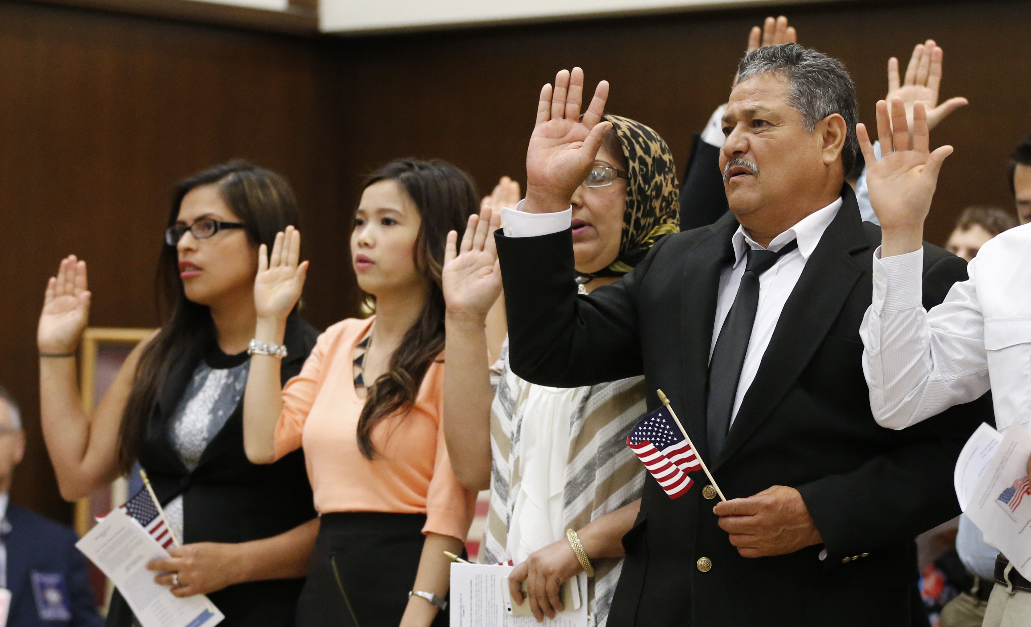 Eduardo Simenta of Mexico, raises his hand as he recites the Oath of Allegiance at a Naturalization Ceremony in Oklahoma City.