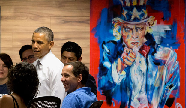 "President Barack Obama stands next to a painting of ""Uncle Sam,"" during a visit with workers at 1776, a hub for tech startups, on Thursday, July 3, 2014, in Washington."