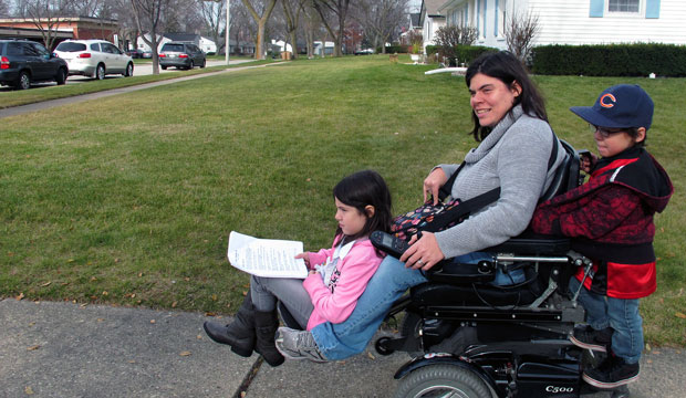 Twins Abigail and Noah Thomas ride on the motorized wheelchair of their mother, Jenn Thomas.