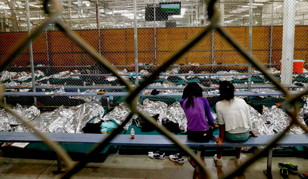 Two young girls sit in their holding area where hundreds of mostly Central American immigrant children are being processed and held at the U.S. Customs and Border Protection Nogales Placement Center on June 18, 2014, in Nogales, Arizona.