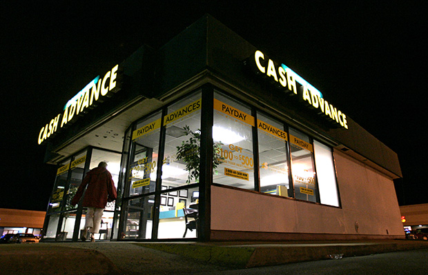 A pedestrian walks to a Cash Advance store in Richmond, Virginia, on Friday, May 19, 2006.