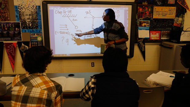 A teacher works with students in an Advanced Placement physics class, February 7, 2014.