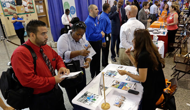Job seekers check out the job opportunities at a hiring fair in Fort Lauderdale, Florida.