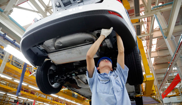 A worker assembles a vehicle on an assembly line at Ford factory in Chongqing, China.